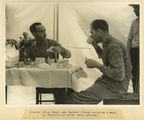 Picture relating to Charleville - titled 'Pilots Scott and Campbell-Black enjoying a meal after landing at Charleville, 1934'