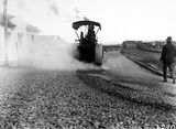 Picture relating to Canberra - titled 'Steamroller spraying tar in Mort Street, Canberra City.'