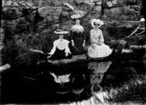 Picture relating to Queensland - titled 'Three elaborately dressed women sitting on the banks of a river, 1910-1920'