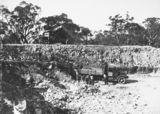 Picture relating to Black Mountain - titled 'Workmen loading a truck in the excavation of the reservoir at Black Mountain. Second truck tipping spoil on the embankment.'