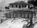 Picture relating to Mount Stromlo - titled 'Construction site, Mount Stromlo with finished building, car and truck in the background.'