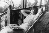 Picture relating to Townsville - titled 'Nurse Nellie Lampton relaxing at home with her photograph album, Townsville, ca. 1919'