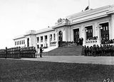Picture relating to Parliament House - titled 'Armistice Day Ceremony with the Royal Military College Cadets on parade in front of Old Parliament House Boy Scouts on the right, View from Parkes Place.'