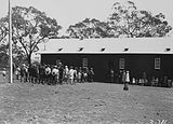 Picture relating to Russell - titled 'School building with children and crowd at the opening of Mount Russell School, Canberra.'