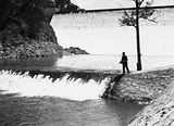 Picture relating to Fisher - titled 'Cotter Dam Wall and stilling pond. Fisherman fly casting into the pond.'