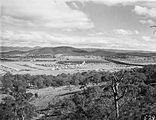 Picture relating to Ainslie - titled 'Braddon and Civic Centre from Mt Ainslie. Ainslie Hotel in the centre. Black Mountain at the rear.'
