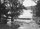 Picture relating to Cotter River - titled 'Cotter Dam Wall overflowing into the stilling pond and the Cotter River'