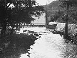 Picture relating to Cotter Dam - titled 'Cotter Dam Wall overflowing into the stilling pond and into the Cotter River'
