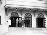 Picture of / about 'Manuka' the Australian Capital Territory - Policeman, bus drivers and civilians on steps of Capitol Theatre, Manuka, for Empire Day celebrations.