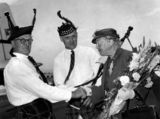 Picture relating to Eagle Farm - titled 'Dame Flora MacLeod being greeted by members of a Scottish Pipe Band at Eagle Farm, 1957'